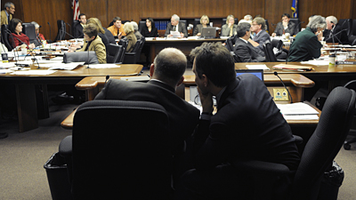 Finance Commissioner Tom Hanson, left, and State Budget Director Jim Schowalter confer as a member of the House Finance Committee makes a comment during the March 10 presentation of the governor