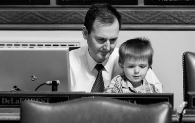 Rep. Chris DeLaForest is joined at his Chamber desk by his son, Will, as the House meets in floor session. (Photo by Tom Olmscheid)