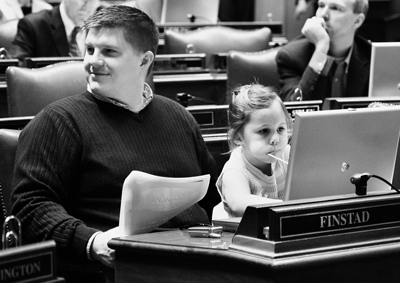 Rep. Brad Finstad holds his daughter, Greta, as she enjoys a sucker and the computer at his desk in the House Chamber. (Photo by Sarah Stacke)
