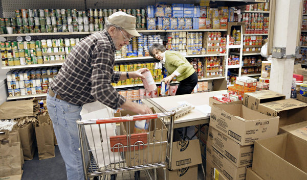Robert Hass, left, packs groceries as fellow volunteer Dorothy King gathers items to fill an order at the Friends in Need Food Shelf in St. Paul Park. (Photo by Tom Olmscheid)