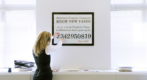 Leesa Paalman, a University of Minnesota intern for Rep. Paul Marquart, updates a sign outside Marquart's office April 23 showing the increase in the state's property taxes since 2002. Marquart chairs the House Property Tax Relief and Local Sales Tax Division. (Photo by Tom Olmscheid)