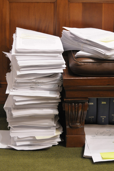 Omnibus bills are subject to amendments, like this stack waiting to be considered for the omnibus tax bill. Amendments can further complicate a member's vote. (Photo by Tom Olmscheid)