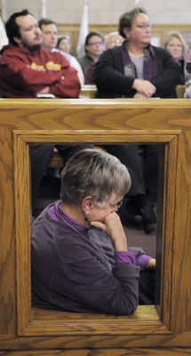 Tina Welch, executive director of the Women�s Health Center in Duluth, leans on a railing as she listens to people testify at a Feb. 20 Budget Listening Session in the Twin Ports. (Photo by Tom Olmscheid)