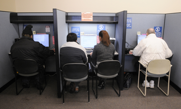 A workforce employee assists a client with filling out a claim, while other clients search job postings on computers at a Workforce Center in St. Paul.