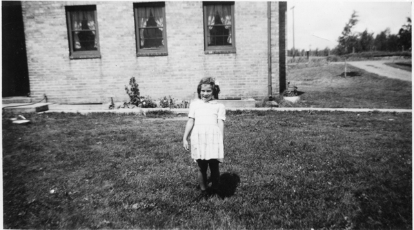 Rep. Mary Murphy, at about age 8, stands in front of her New Deal house in Hermantown. She has lived in the house her entire life. (Photo courtesy of Rep. Mary Murphy)