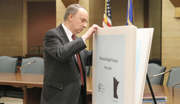 State Economist Tom Stinson takes a peek at the charts and graphs that illustrate the state budget forecast prior to a March 3 news conference. (Photo by Tom Olmscheid)