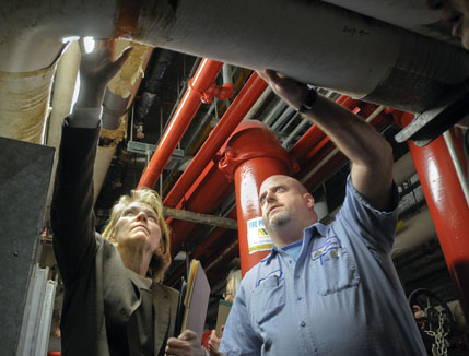 Capitol Plant Management Engineer Dave Albien and Rep. Mary Kiffmeyer examine an aging heating system during a March 3 tour of Capitol building deficiencies by the House State Government Finance Division. (Photo by Andrew VonBank)