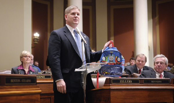 House Minority Leader Kurt Zellers holds up a backpack saying, �I�m ready to get to work,� after being congratulated by House Majority Leader Tony Sertich on being elected minority leader. Rep. Marty Seifert resigned as minority leader following the 2009 legislative session to concentrate on his run for governor. (Photo by Tom Olmscheid)