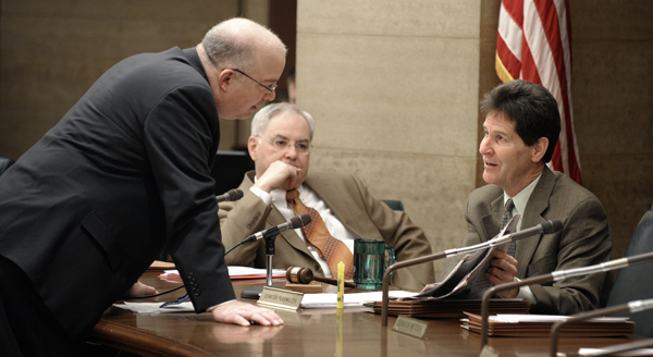 Prior to a Feb. 16 hearing of the LCPFP Subcommittee on a Balanced Budget, House Finance Committee Chairman Rep. Lyndon Carlson, Sr., center, listens as he and Senate Majority Leader Larry Pogemiller, right, question Minnesota Management & Budget Commissioner Tom Hanson on the use of federal funds to balance Gov. Tim Pawlenty's supplemental budget proposal. (Photo by Tom Olmscheid)