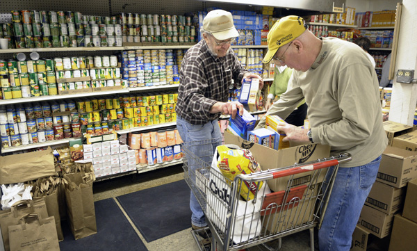 Volunteers at the Friends in Need Food Shelf in St. Paul Park pack bags of groceries for recipients. (Photo by Tom Olmscheid)