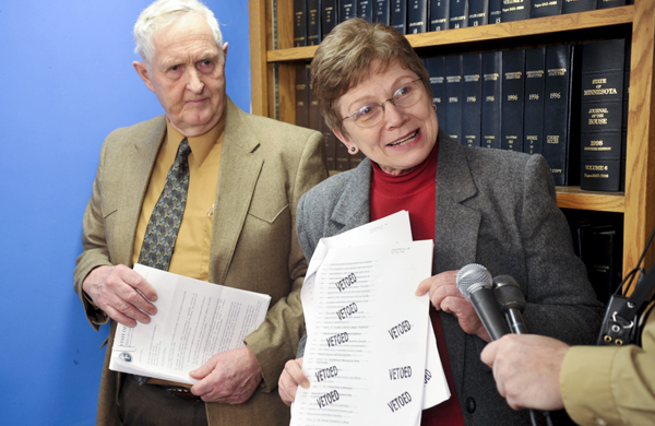 At a March 15 press conference, Rep. Alice Hausman shows a section of the capital investment law that contains several gubernatorial line-item vetoes to Minnesota State Colleges and Universities systems projects. Hausman and Sen. Keith Langseth, left, sponsor the law that received a $313 million cut by Gov. Tim Pawlenty. (Photo by Tom Olmscheid)