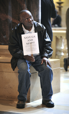 Eric Vaye, a resident at the House of Charity in Minneapolis, rests on one of the granite columns in the Capitol Rotunda April 26 while holding his sign urging members to save General Assistance and the Minnesota Family Investment Program. (Photo by Tom Olmscheid)