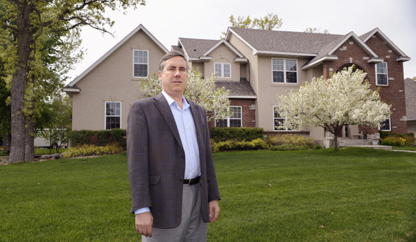 Paul Stutler stands in front of his Eagan home that suffered severe water damage. (Photo by Tom Olmscheid)