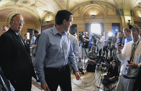 Senate Minority Leader David Senjem, left, waits as Gov. Tim Pawlenty turns back to answer one more reporter's question May 16 after explaining his position on negotiations with the Legislature to balance the state's budget. (Photo by Tom Olmscheid)