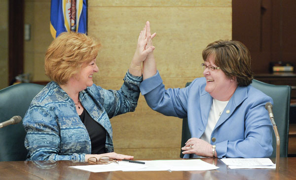 "In a bi-partisan gesture, Rep. Marsha Swails, left, and Rep. Carol McFarlane, right, give each other a ""high five"" after the conclusion of a May 3 conference committee that meant the completion of a bill the two co-authored that would establish a collaborative governance council. (Photo by Andrew VonBank)"