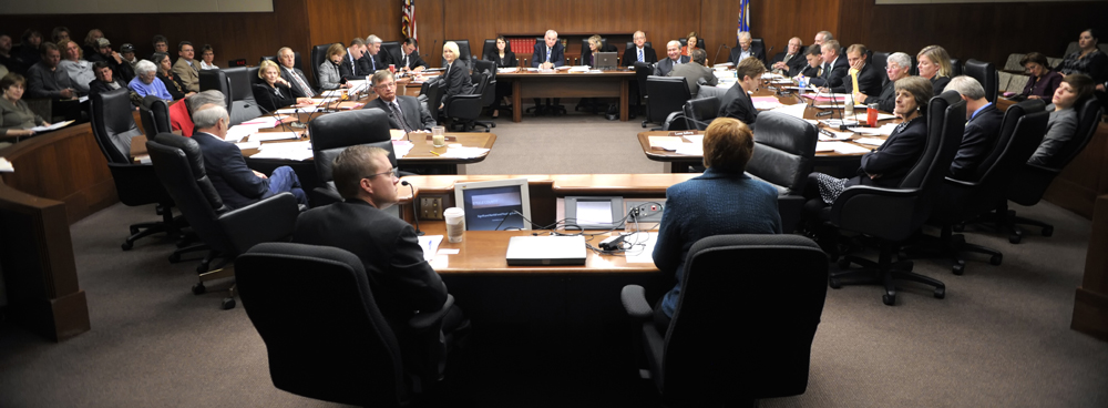 Rep. Kory Kath, left, and members of the House Finance Committee listen as Kris Eide, right, director of emergency services for the Department of Public Safety, talks about the natural disaster relief package. (Photo by Tom Olmscheid)