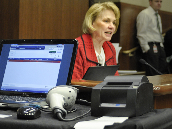 Rep. Mary Kiffmeyer shows members of the House Government Operations and Elections Committee a demonstration of the electronic polling machine and new voter ID during Feb. 8 discussion of a bill that would require voters to show a picture identification before receiving a ballot. (Photo by Andrew VonBank)