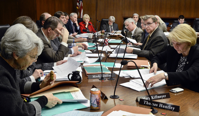 Members of the House Ways and Means Committee wade through bill copies and amendments on the committee table during the March 23 hearing. (Photo by Andrew VonBank)
