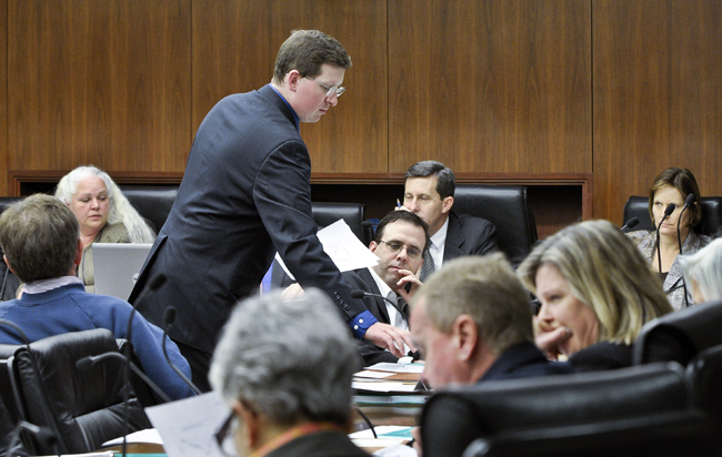 House Page Michael Mullen passes out amendments to the omnibus tax bill during the March 23 meeting of the House Ways and Means Committee. (Photo by Andrew VonBank)