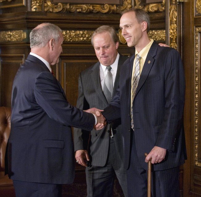 Rep. Rod Hamilton, right, gets a handshake from Gov. Mark Dayton and a pat on the back from 