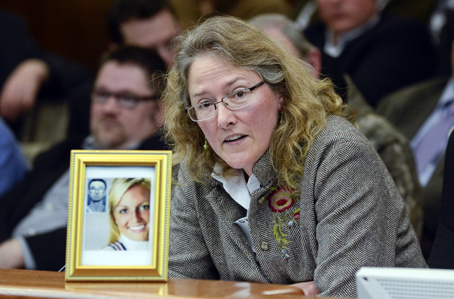 Displaying a photograph of a gun victim and her shooter, Heather Martens, executive director of Protect Minnesota, testifies before a packed House Public Safety and Crime Prevention Policy and Finance Committee April 28 in opposition to a bill that would amend the law on use of force in defense of a person's home. (Photo by Andrew VonBank)