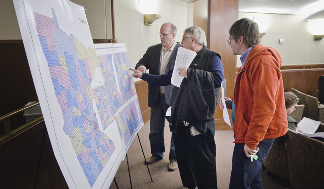Tim Kinley of Maplewood, from left, Bob Murray of Roseville and Curtis Neff of St. Paul take a look at the proposed legislative district maps prior to a hearing of the House Redistricting Committee May 3. (Photo by Tom Olmscheid)