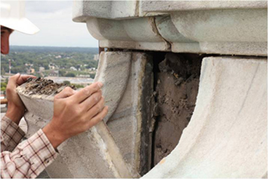 A worker examines deterioration around a panel of marble near the finial (the top of the Capitol dome). The building's damaged masonry is among the many problems lawmakers hope to address. (Photo courtesy of the Department of Administration)