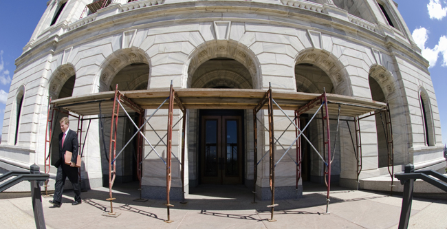 A visitor passes under scaffolding covering the Capitol's west entrance. Fears of injury caused by deteriorated stonework falling off the marble exterior prompted officials to place protective structures around the building. (Photo by Tom Olmscheid)