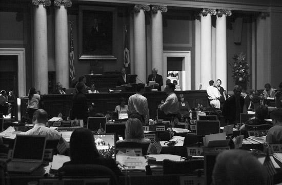 Rep. Karen Klinzing and Shawn M. Peterson, director of majority legislative services, talk in a beam of light shining on the right side of the front desk in the House Chamber during a July 13, 2005 blackout at the Capitol during a special session. (Photo by Tom Olmscheid)