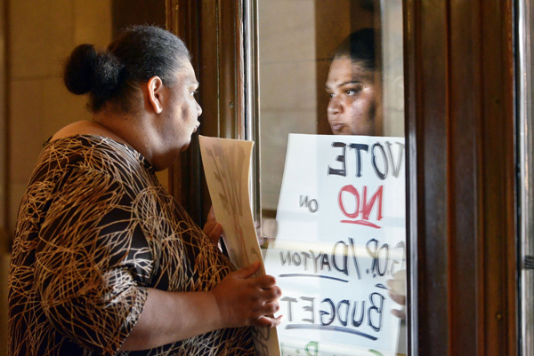 Representing the Welfare Rights Committee, Angel Buechner of Minneapolis waits for legislators after being among the first to enter the Capitol July 19, 2011. Doors to the building had been locked since the state government shutdown began July 1. (Photo by Andrew VonBank)