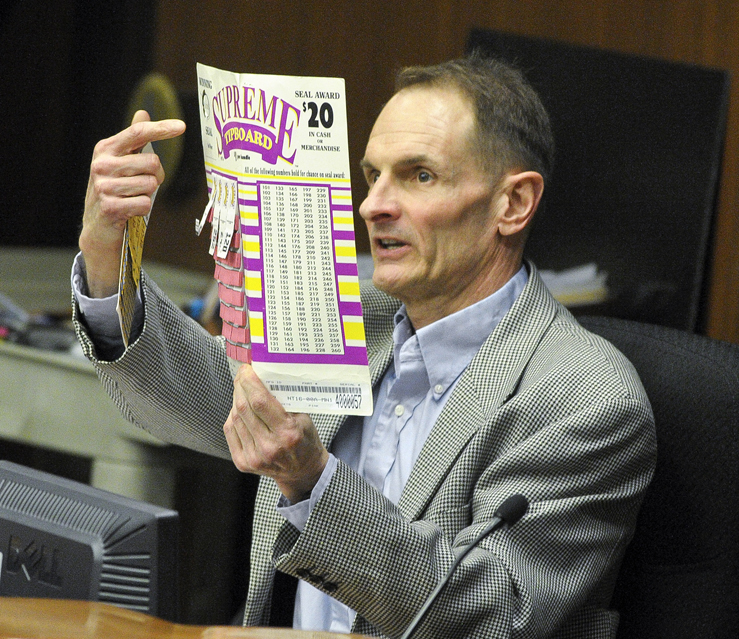 King Wilson executive director of Allied Charities, shows members of the House Commerce and Regulatory Reform Committee an example of tip board numbers during discussion of a bill that help would provide funding for a new stadium to house the Minnesota Vikings. (Photo by Andrew VonBank)