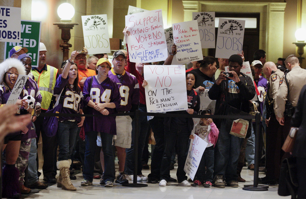 Vikings stadium supporters and opponents stand side-by-side outside the House Chamber May 7. The House passed its version of the stadium bill that day. The final bill was passed three days later. (Photo by Paul Battaglia)