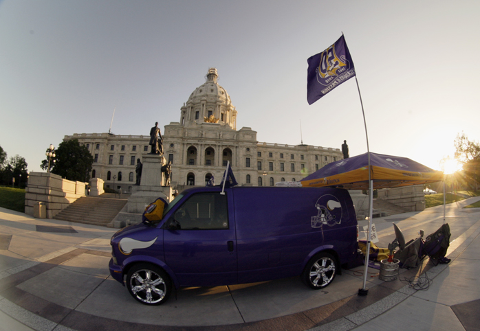 "As the sun rises on the Capitol May 10, superfan Larry Spooner is asleep on the ground at the back of the van that had been the headquarters for fans from the ""Vikings World Order."" Spooner has advocated for a new stadium for more than a decade. (Photo by Paul Battaglia)"